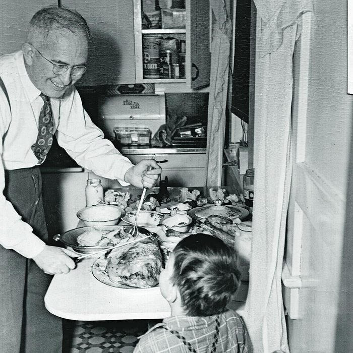 Older man carving tourkey while smiling at young boy 1930s
