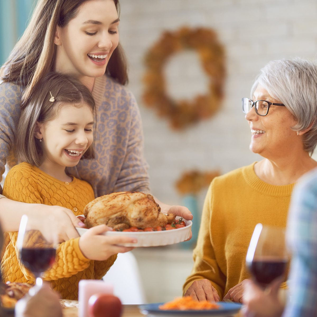 Mom and daughter presenting turkey to grandma