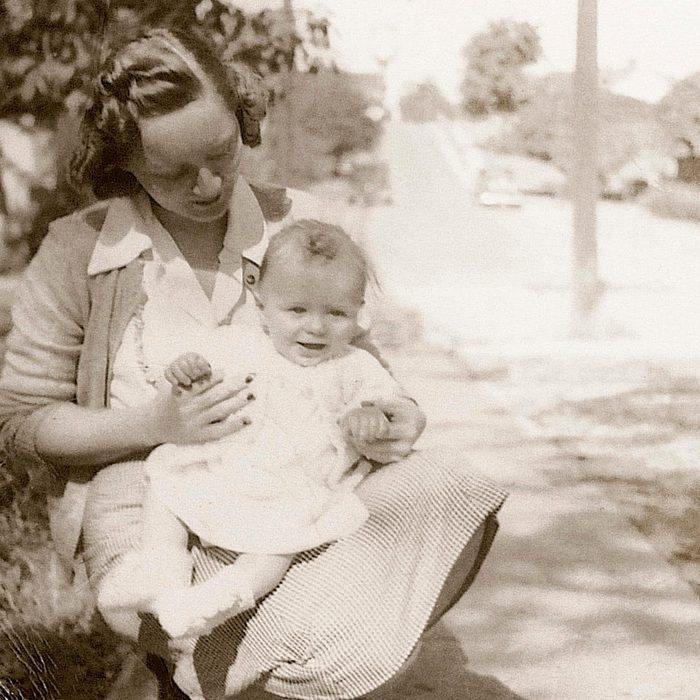 1930s mother crouched down holding her baby