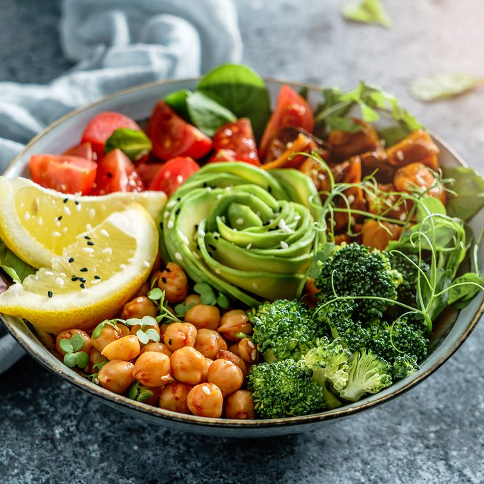 Buddha bowl salad with baked sweet potatoes, chickpeas, broccoli, tomatoes, greens, avocado, pea sprouts on light blue background with napkin.
