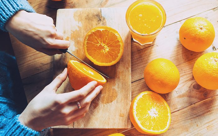 Person cutting to make juice from fresh oranges on wooden table