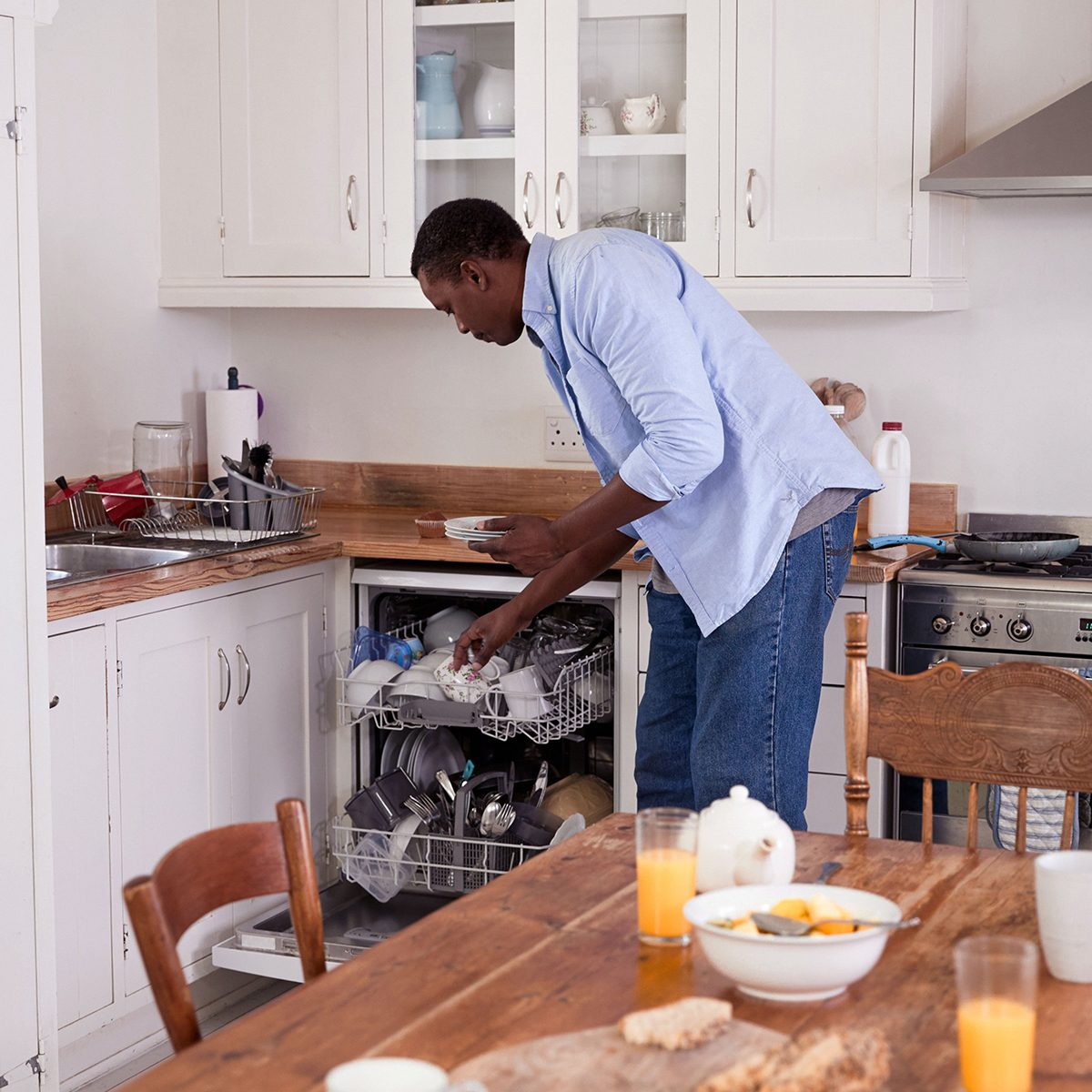 Man loading dishes into a very full dishwasher