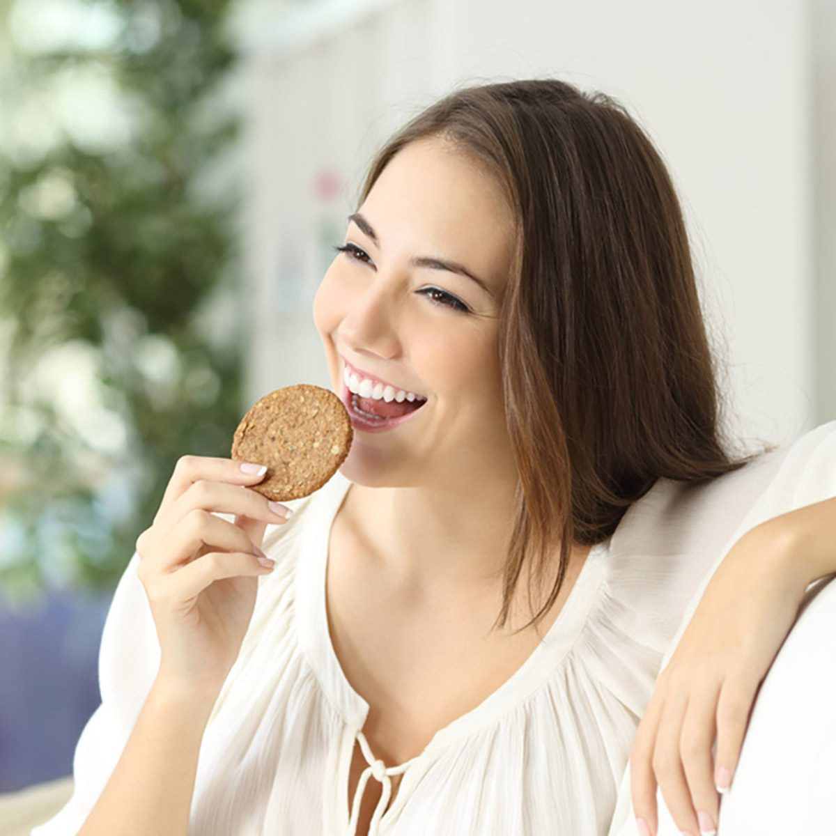Happy girl eating a dietetic cookie sitting on a couch at home