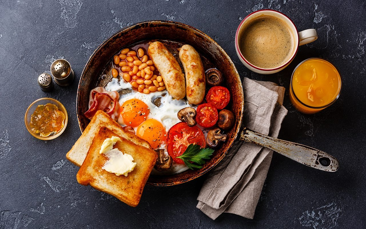 Full English breakfast in pan with fried eggs, sausages, bacon, beans, toasts and coffee on dark stone background