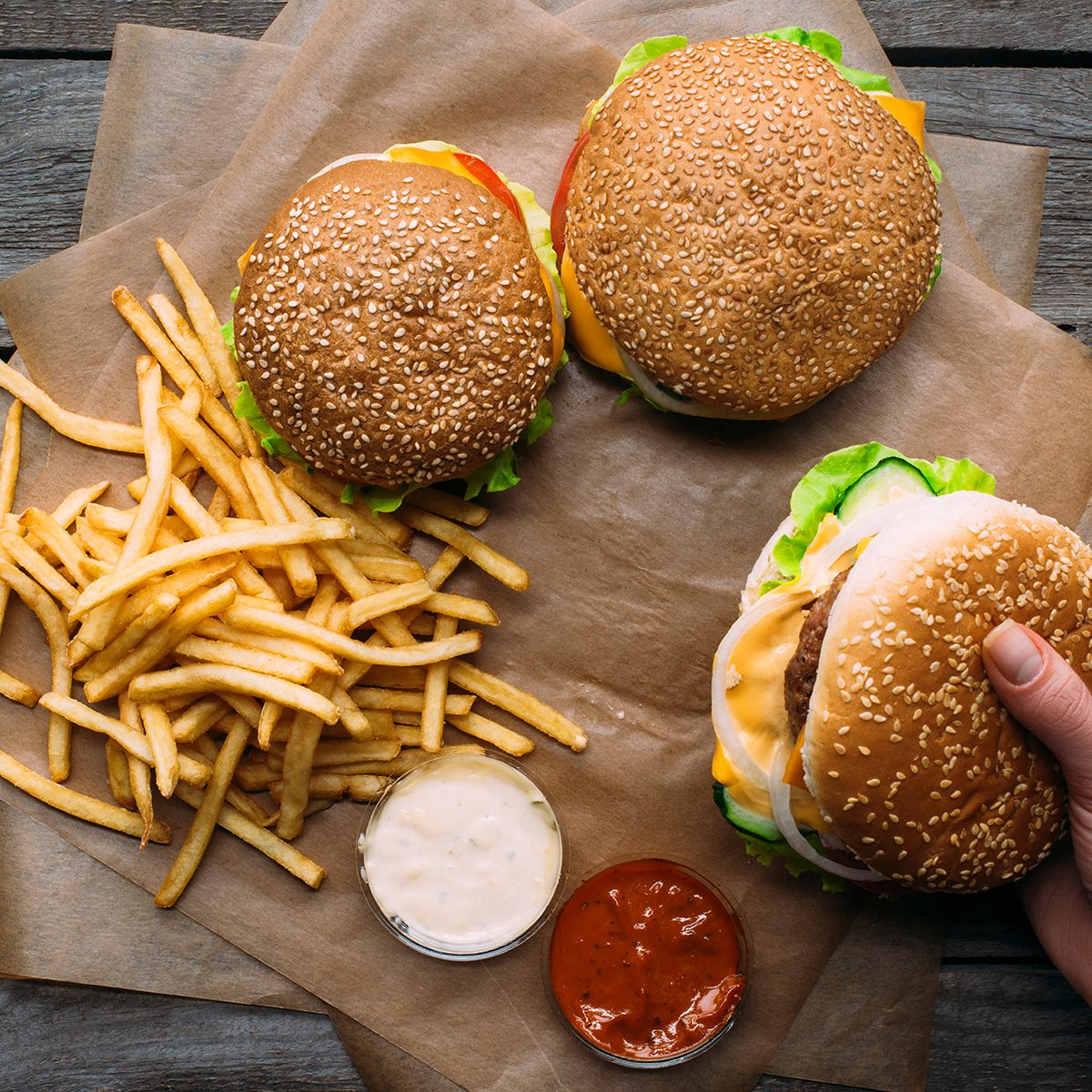 top view of hand with hamburgers, french fries and sauces on baking paper on wooden tabletop