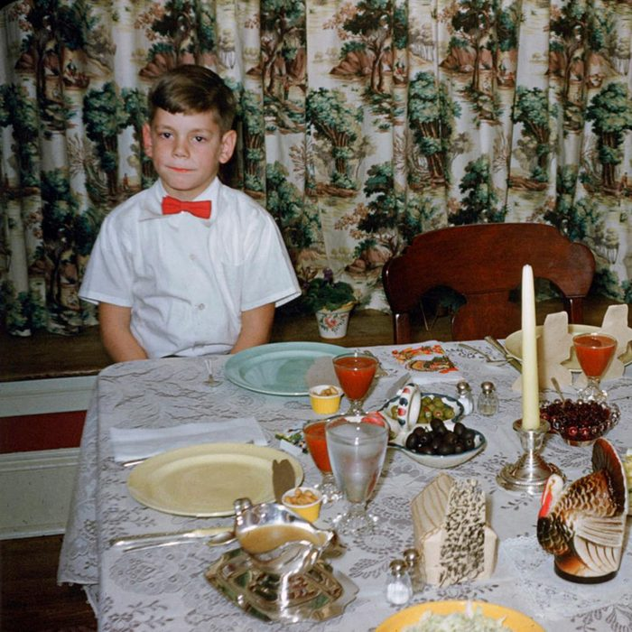 bored boy in red bow tie sits patenintly at thanksgiving dinner table