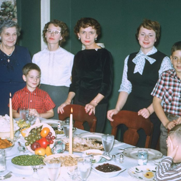 family poses around the thanksgiving table
