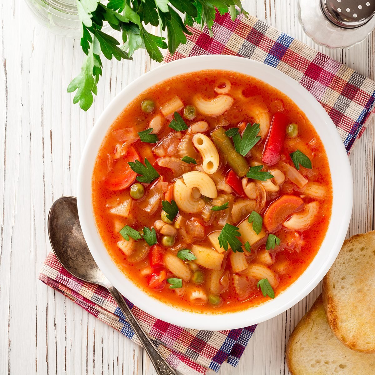 Italian minestrone soup on white wooden background.