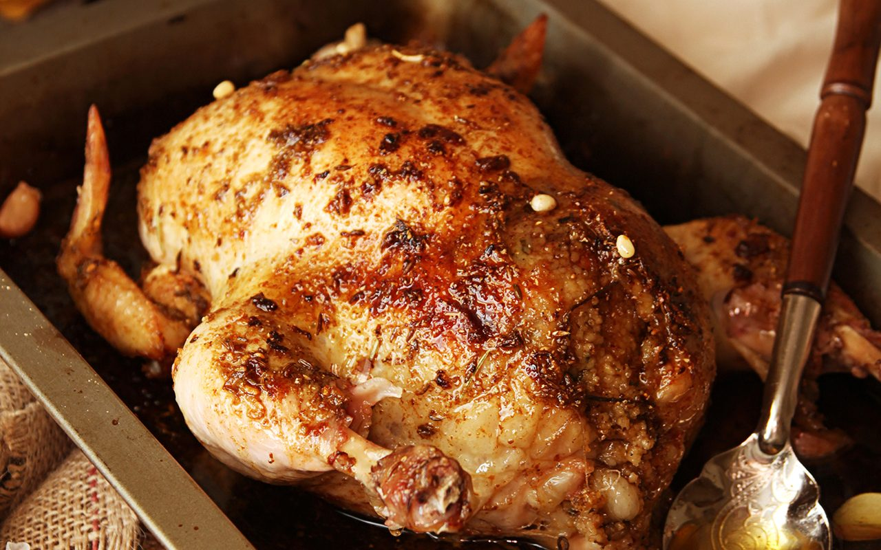 Roasted small turkey for celebration Christmas in roasting pan on old rustic wooden table. Stuffed with couscous with a fig, prunes, dried apricots, almonds and pine nuts.