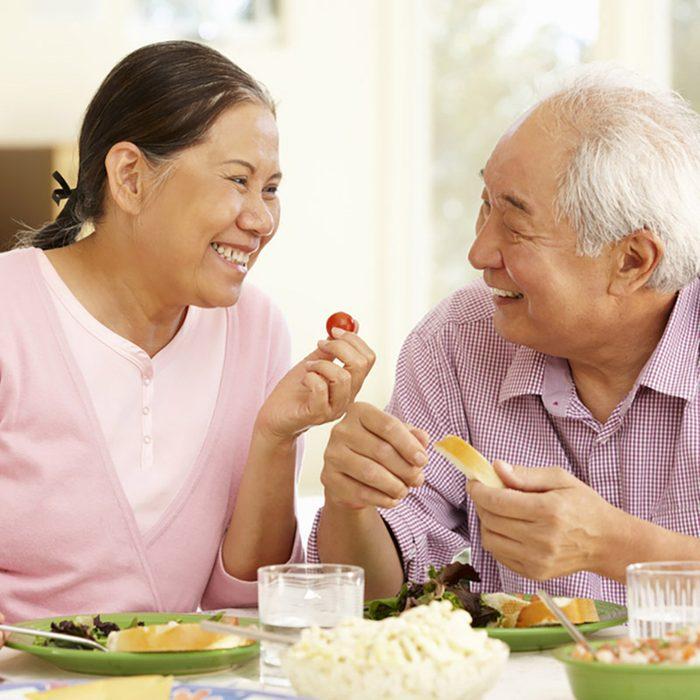 Senior asian couple sharing meal at home