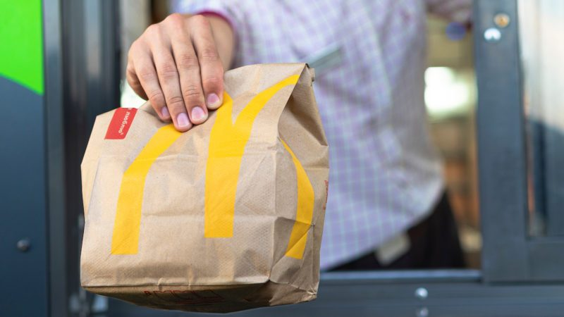 McDonalds worker holding bag of fast food. Hand with a paper bag through the window of mcdonalds car drive thru service.