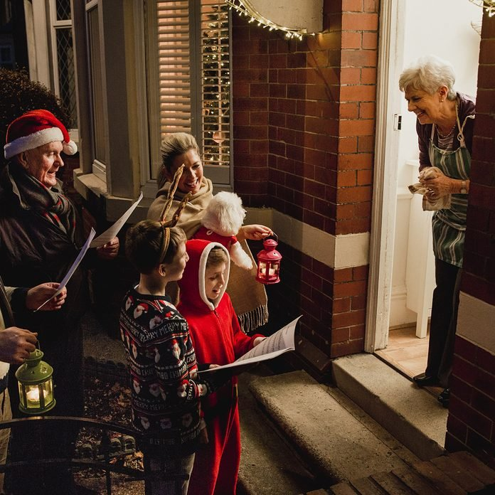 Three generation family are doing door-to-door carol singing. There is a senior woman at the door, appreciating their singing.; Shutterstock ID 672017293; Job (TFH, TOH, RD, BNB, CWM, CM): Taste of Home