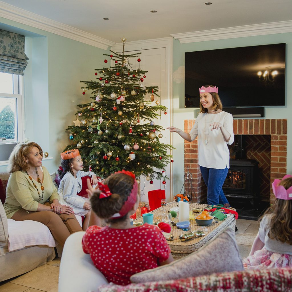 Family are playing charades at christmas time in the living room of their home. It's the mother's turn and everyone is trying to guess. ; Shutterstock ID 723224050; Job (TFH, TOH, RD, BNB, CWM, CM): Taste of Home