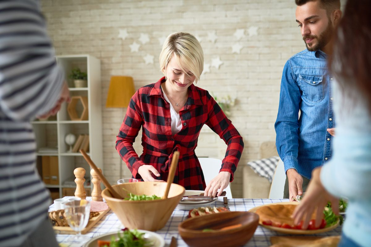 Group of young people preparing dinner for festive celebration together, focus on happy young woman setting up table