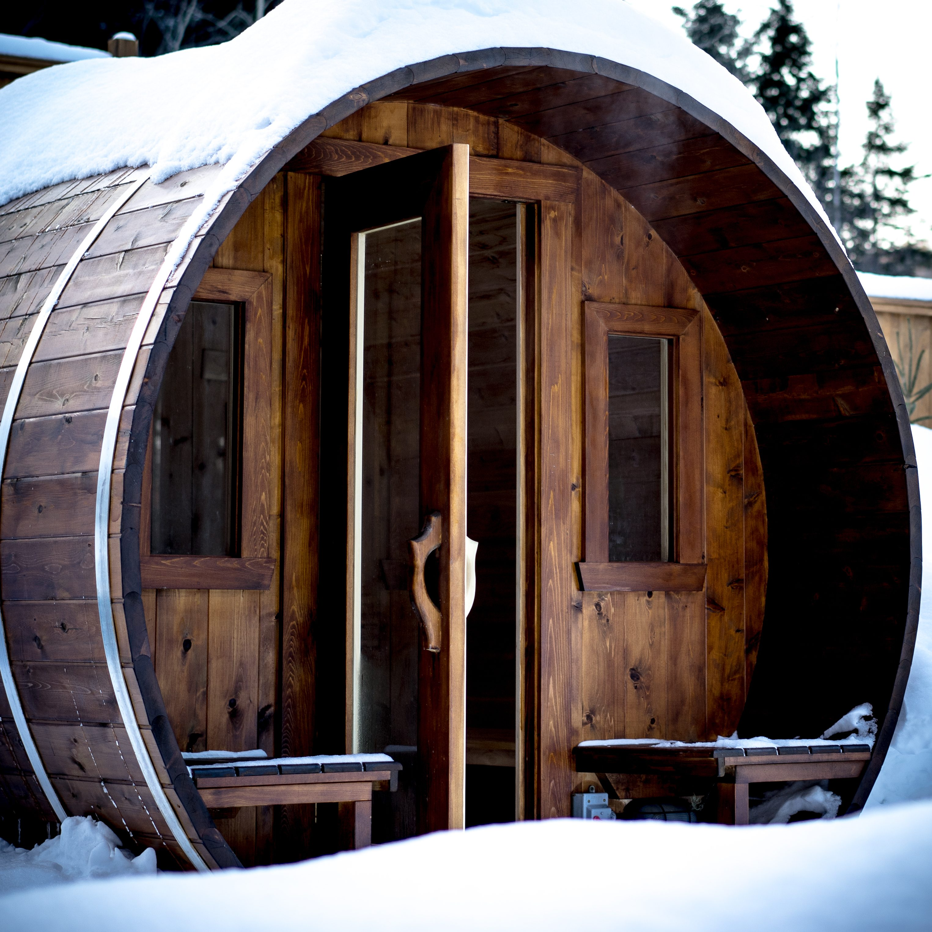 wooden outdoor sauna during a cold winter day with steam going out of the open door