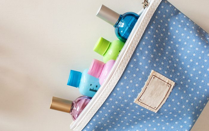 Blue travel toiletry bag with travel toiletries, small plastic bottles of hygiene products and perfume on white background.
