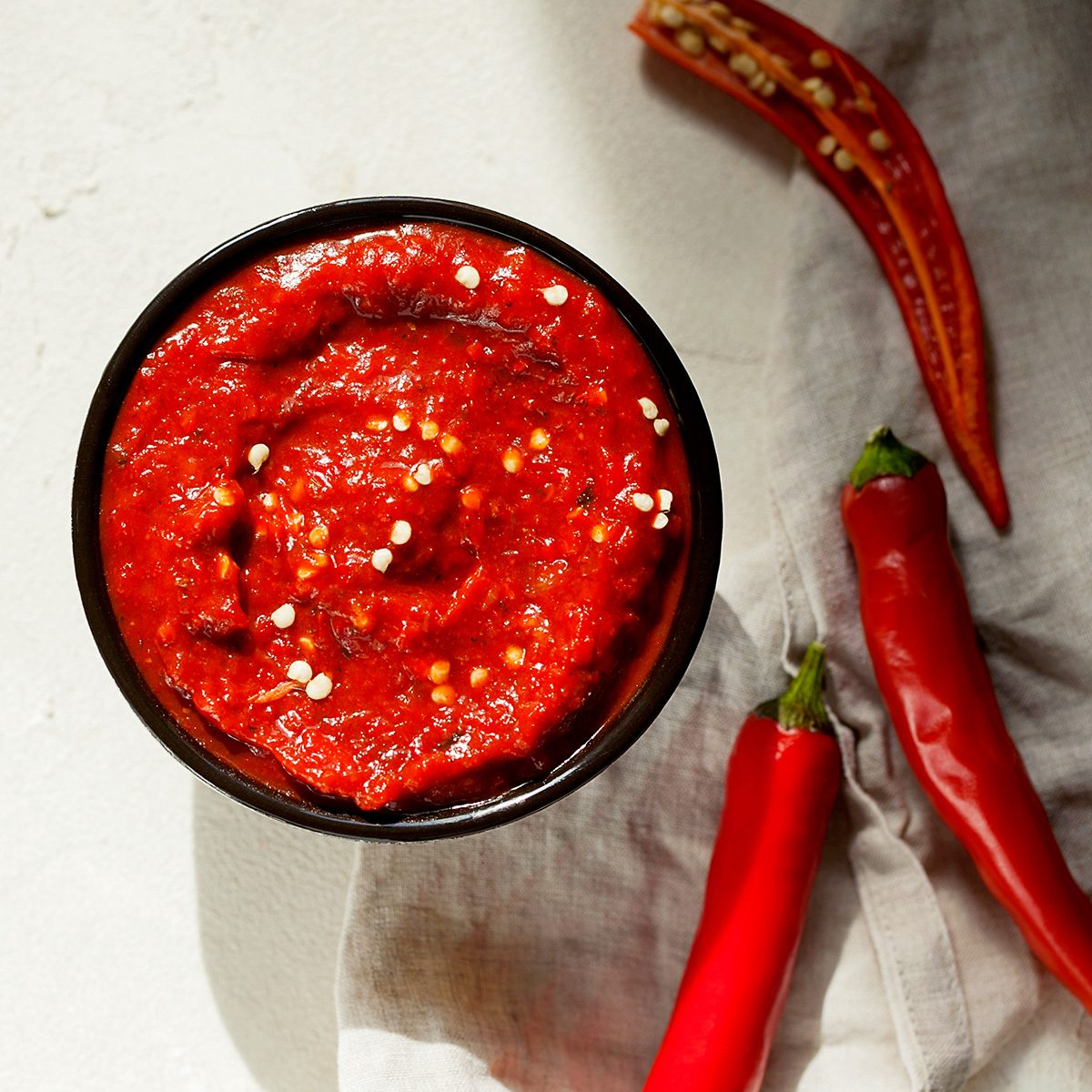 Traditional homemade rose harissa-hot chili pepper sauce paste with garlic and olive oil in small bowl on white plaster background
