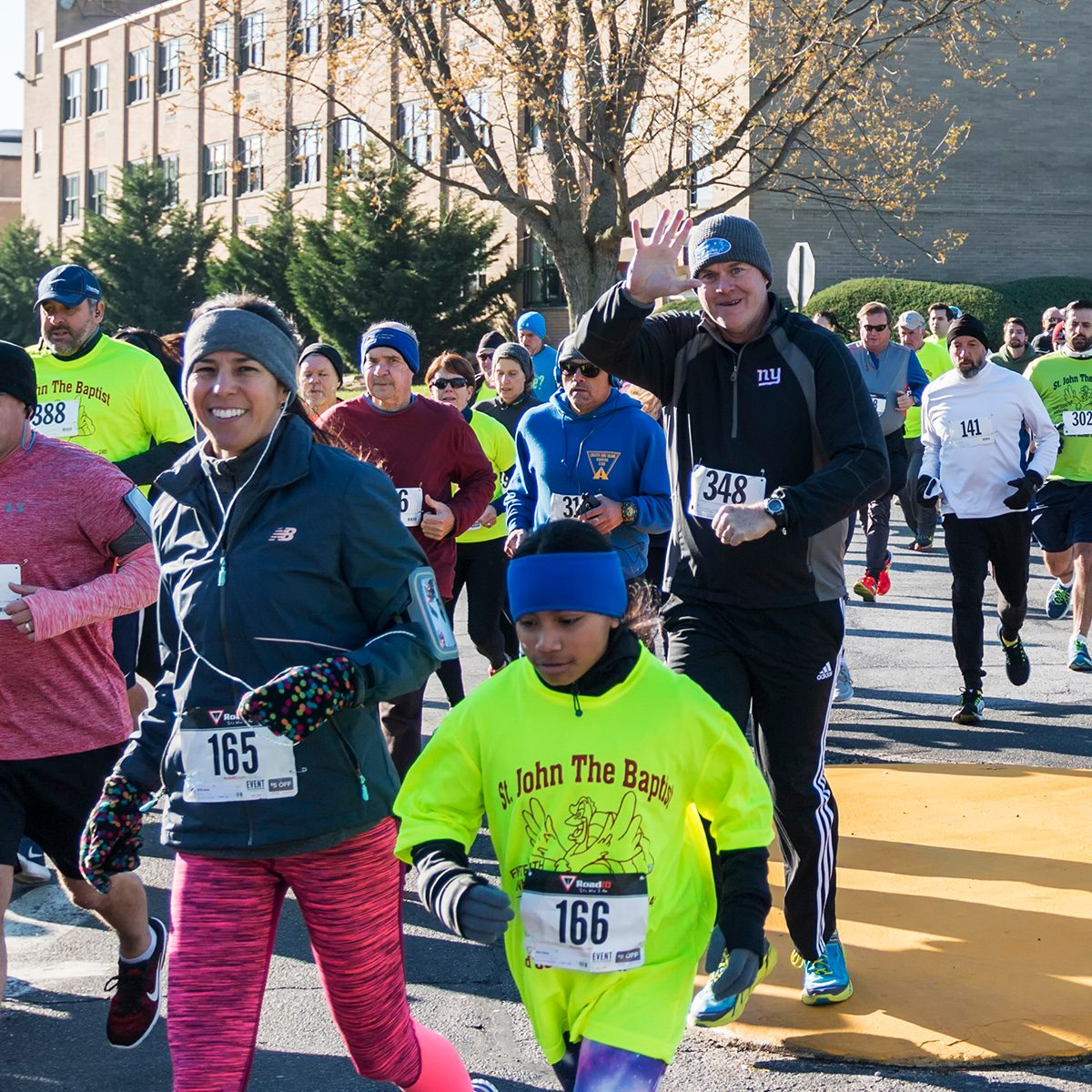 Runners wave to the camera at the start of the Run Your Turkey Off 4K race, the day after thanksgiving.
