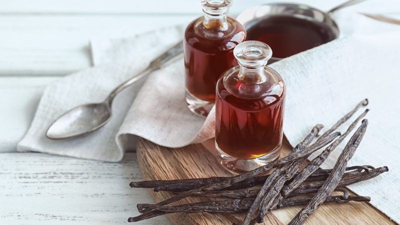 Bottles with aromatic extract and dry vanilla beans on board