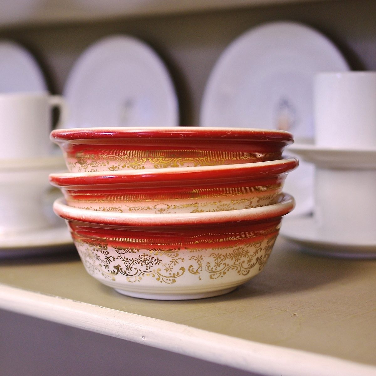 Vintage Stack of Bowls: close up of three orange & white bowls with a gold flowered pattern, stacked three high resting on a shelf amongst a backdrop of assorted white dishes at a thrift store.