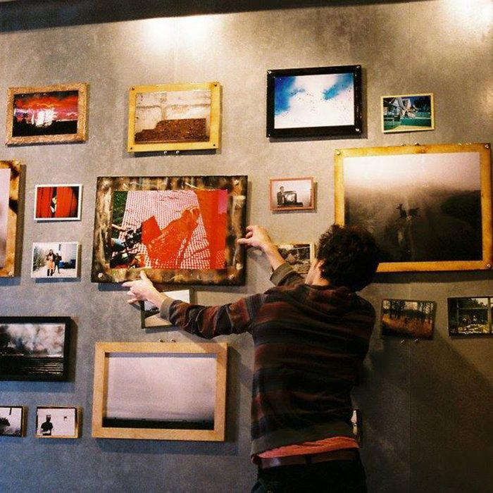 Someone hanging art at the Art*Bar