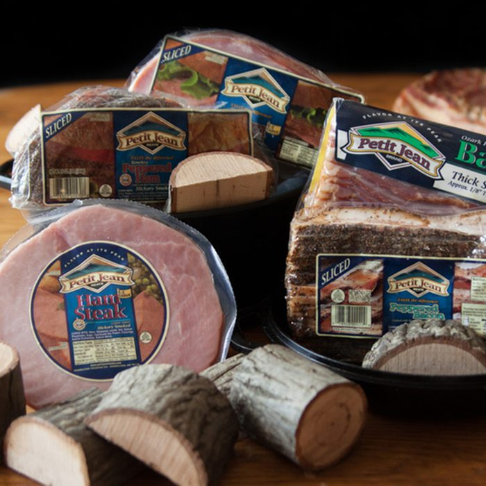 Petit Jean Meat brand ackages of pork on table with wood