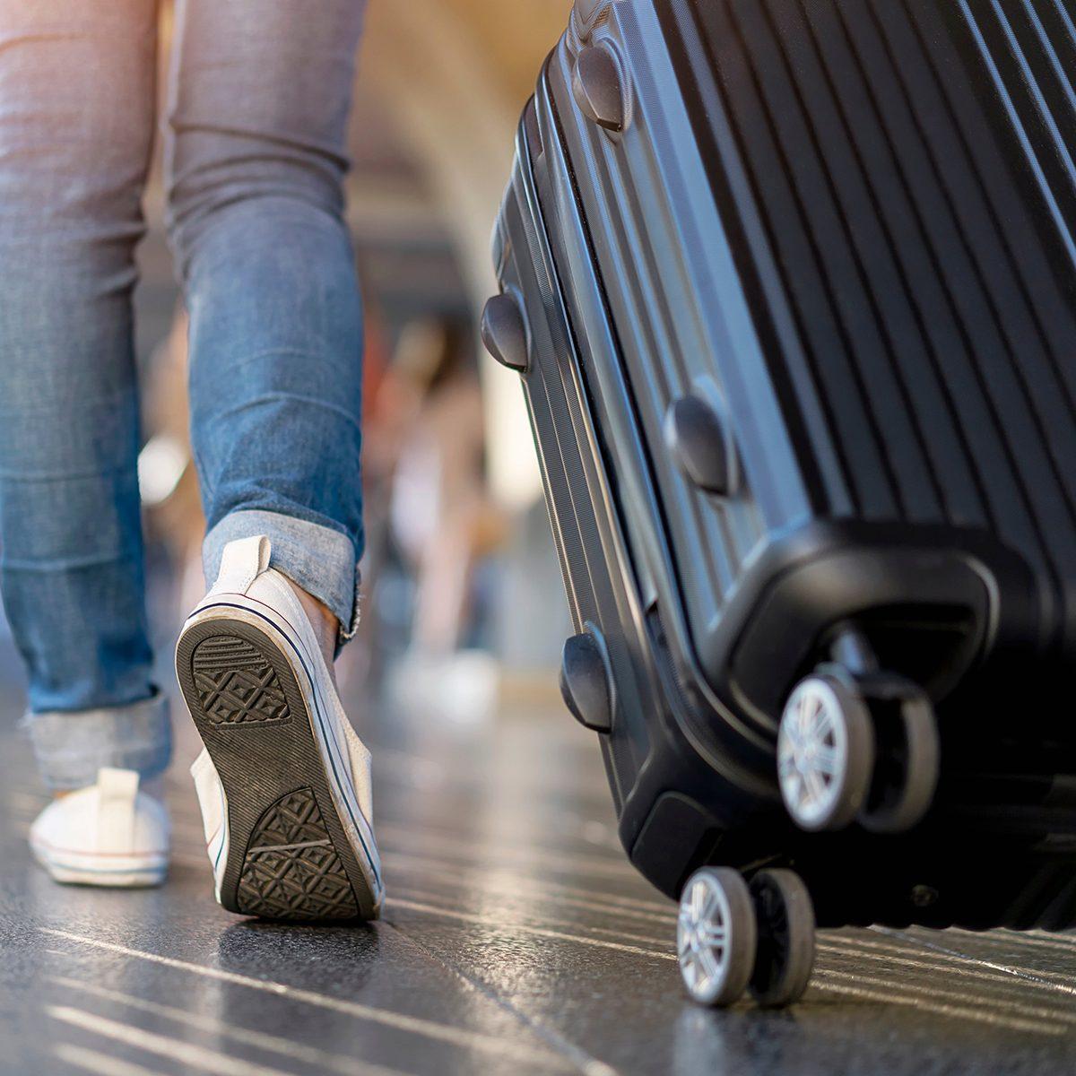 Person wheeling luggage through airport