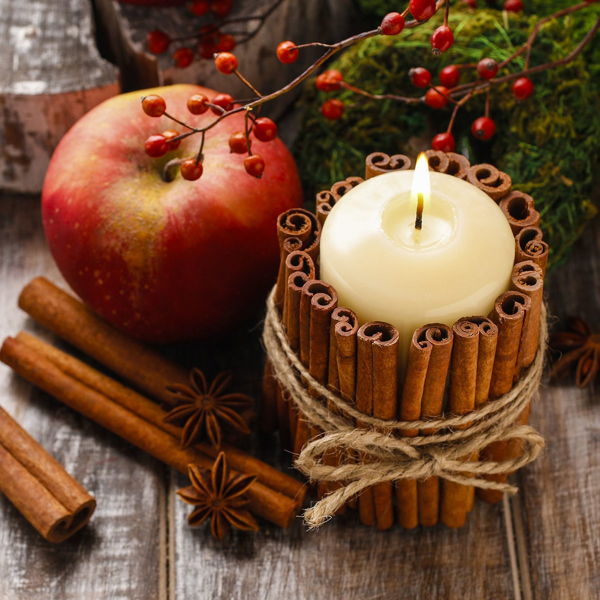 Candle decorated with cinnamon sticks and red apples, christmas decoration