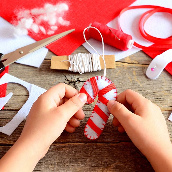 Child holds Christmas felt candy cane in his hands. Materials and tools to create Christmas tree decorations.