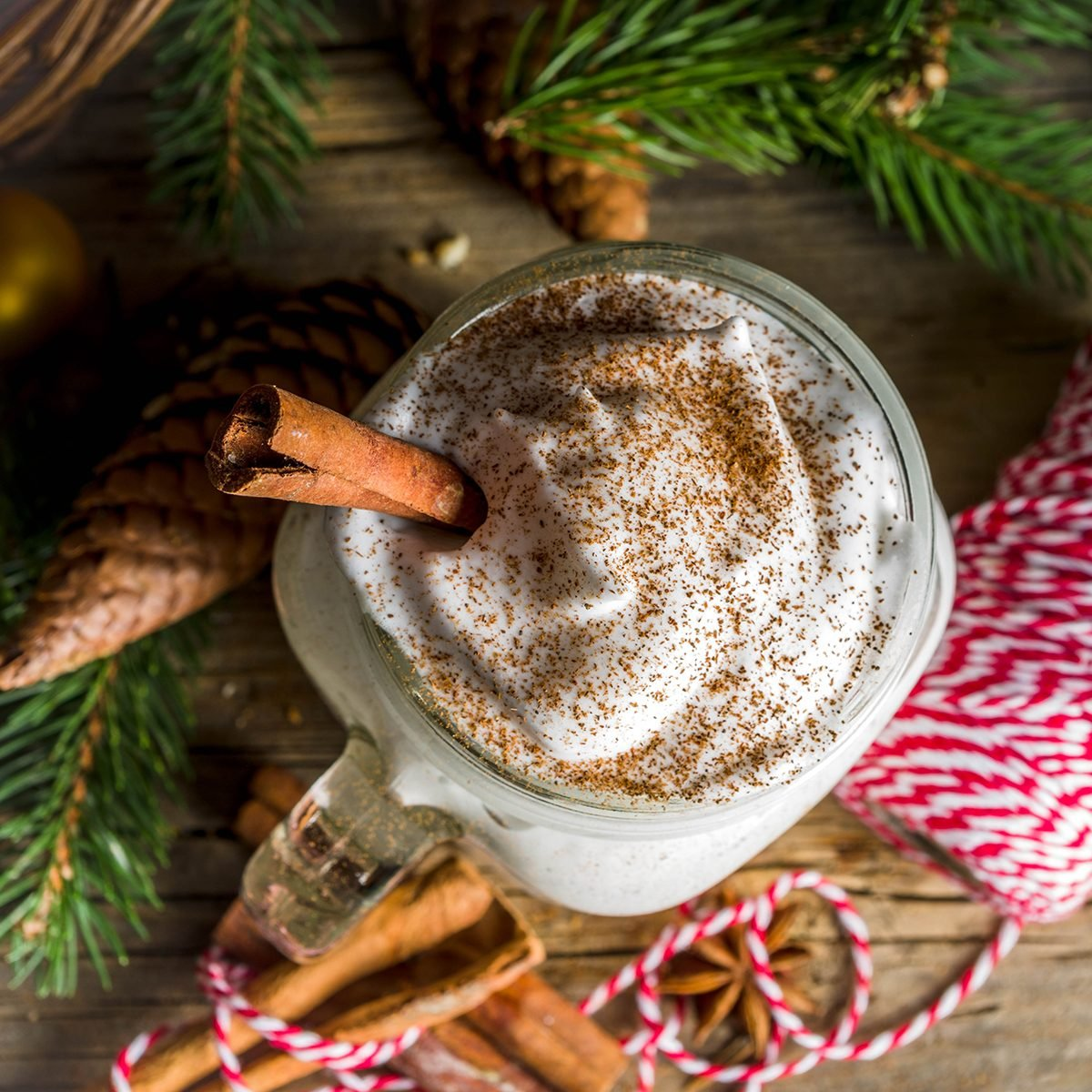 Christmas Tom and Jerry cocktail, whipped cream eggnog with spices, dairy milk beverage, with christmas decorations, rustic wooden background