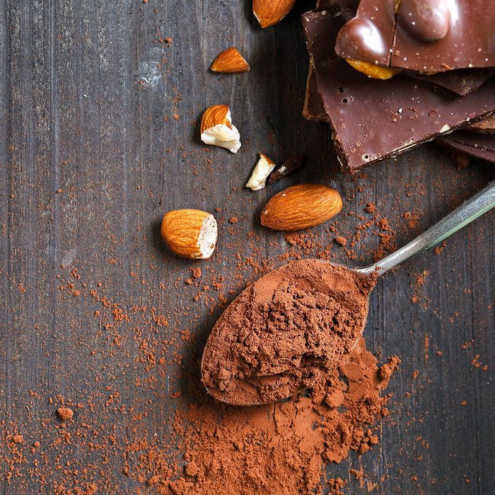 Cocoa Powder and Dark Chocolate almond on black wood table