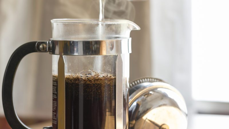 Coffee brewing in a French press in warm morning light