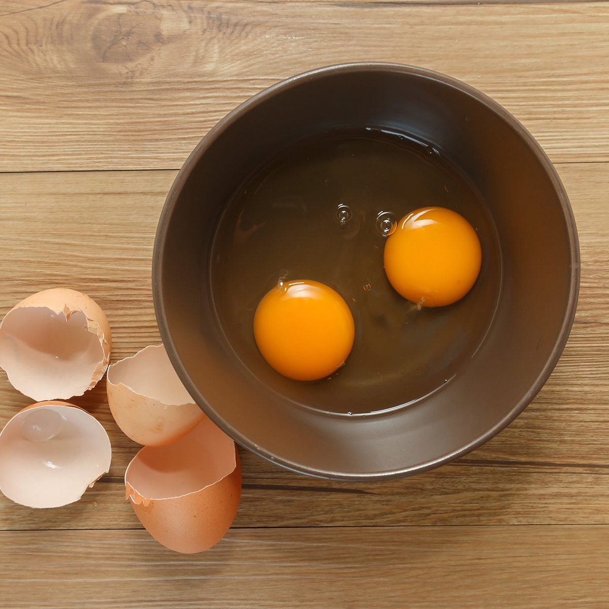 Cracked eggs with yolks in a bowl