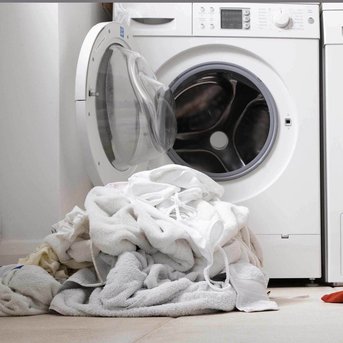 Laundry room washing machine pile of white clothes