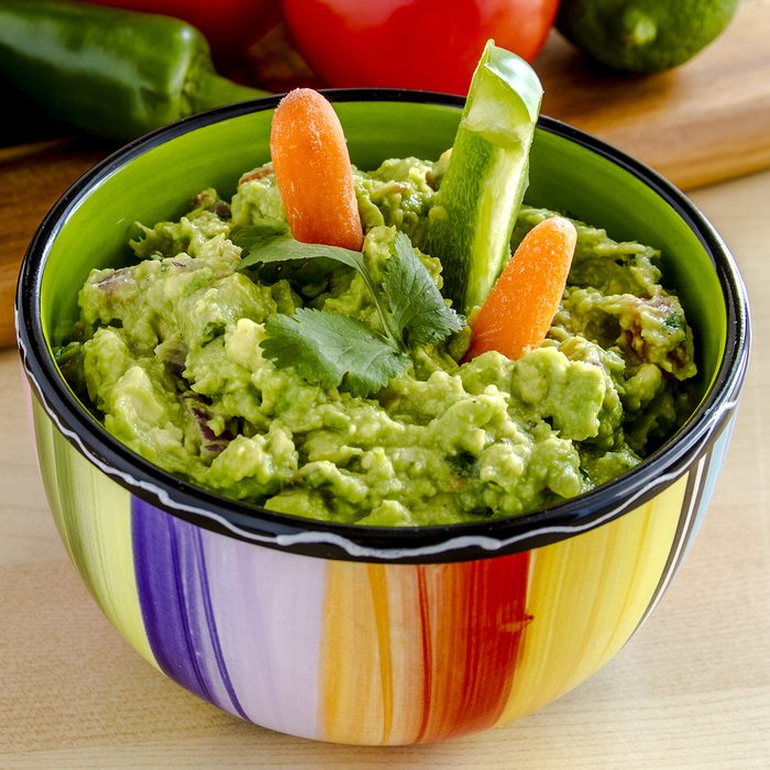 Fresh chunky guacamole in colorful bowl garnished with raw carrots and green peppers and cilantro