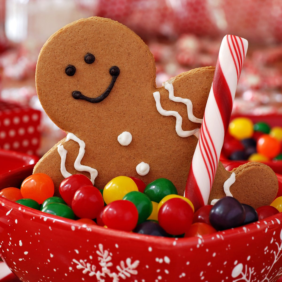 Fun image of smiling gingerbread man with peppermint stick in holiday snowflake dish with colorful candy.