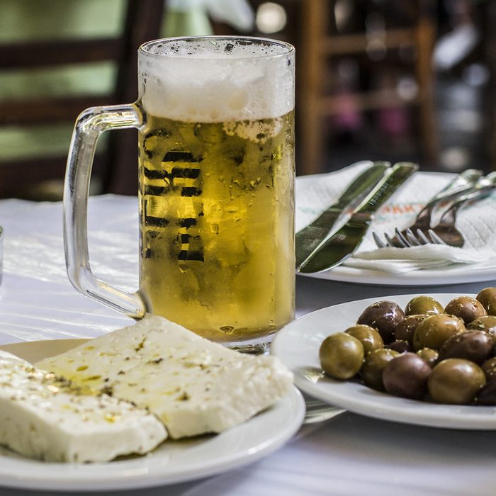 Greek famous food: cheese and olives with a glass of beer on the table, Athens, Greece