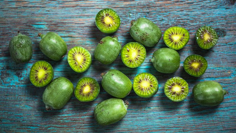 Kiwi berries on vibrant wooden board