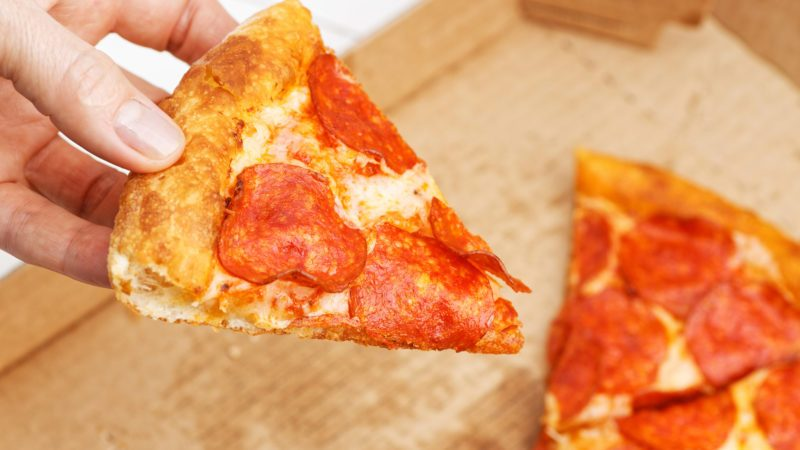 Closeup slice of italian pepperoni pizza in hand and open box with pizza leftovers on blurred background; Shutterstock ID 1508864222; Job (TFH, TOH, RD, BNB, CWM, CM): TOH winter pizza delivery