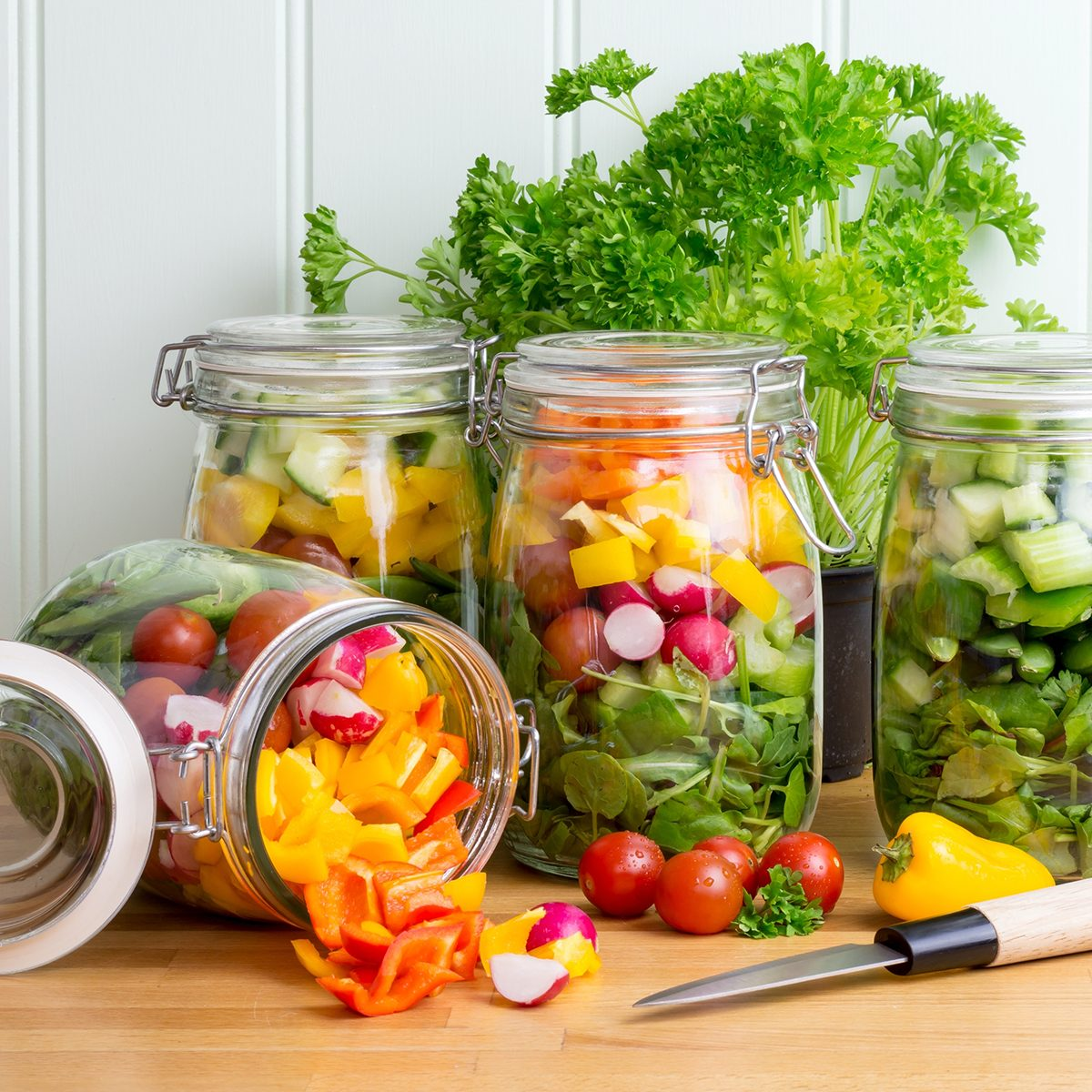 Prepared salad in glass storage jars. One jar tipped on side spilling contents. Meal prep.