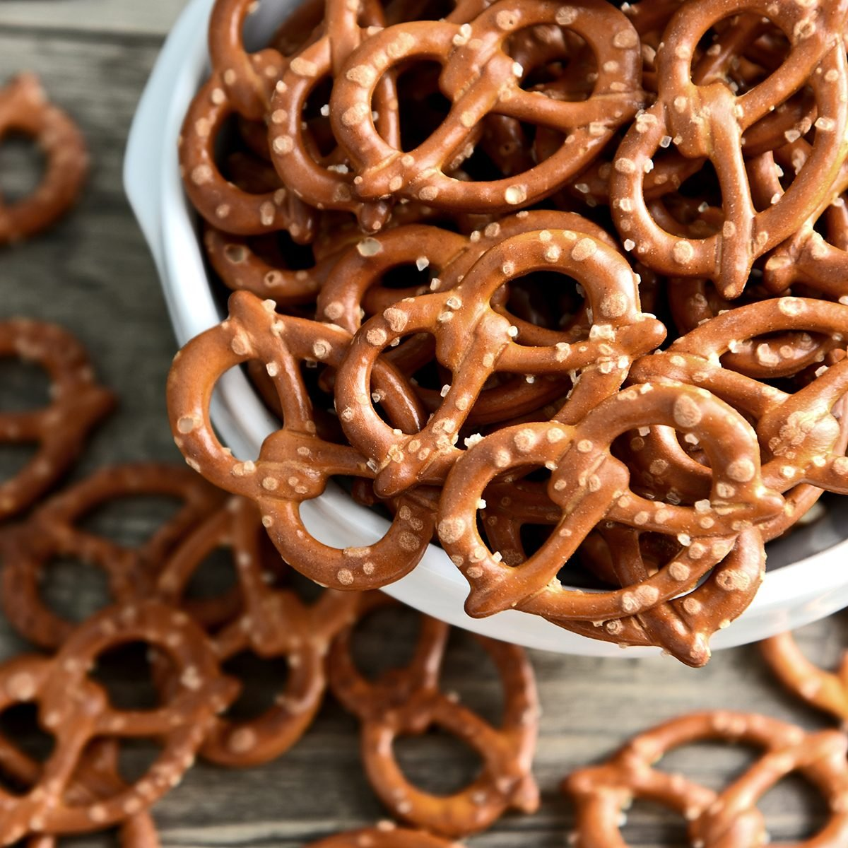 Hard Pretzels or Salted pretzels snack for party in white bowl on wooden floor