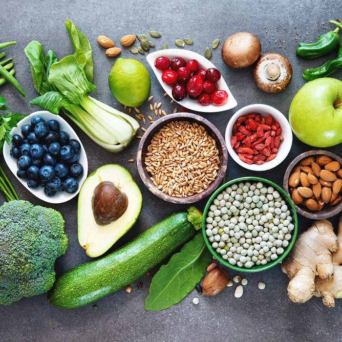 Healthy food selection with fruits, vegetables, seeds, superfood, cereals on gray background