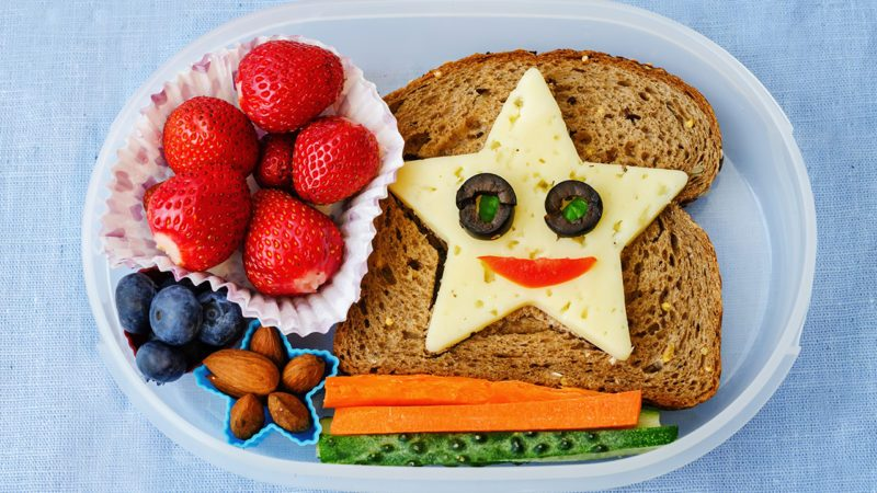 school lunch box for kids with food in the form of funny faces. the toning.