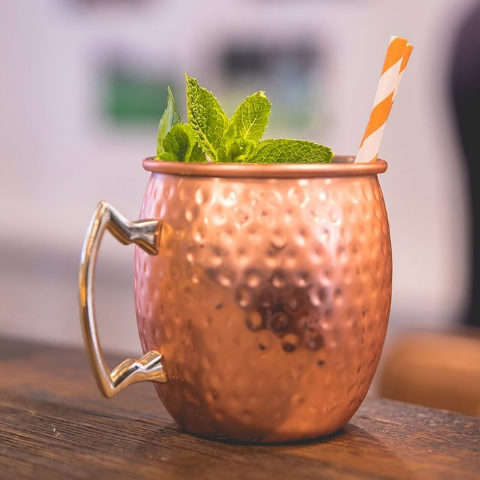 Close up on a copper cup with Moscow Mule cocktail, fresh mint as decoration and a white and orange carton straw; Shutterstock ID 1165209037; Job (TFH, TOH, RD, BNB, CWM, CM): TOH