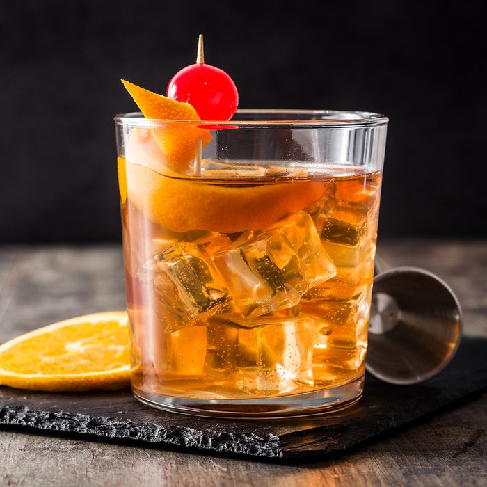 Old fashioned cocktail with orange and cherry on wooden table. Copyspace; Shutterstock ID 1338703802; Job (TFH, TOH, RD, BNB, CWM, CM): TOH