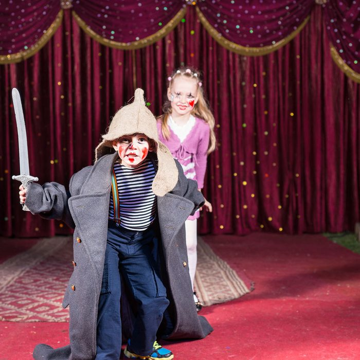 Cute talented boy playing the role of a brave Russian warrior fighting with a sward to defense his beautiful wife, in a theatrical performance at school; Shutterstock ID 275612612