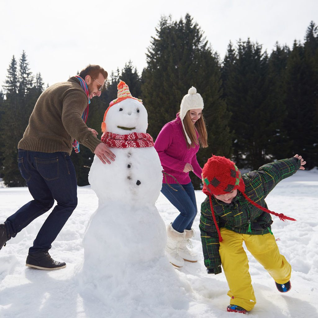 happy young family playing in fresh snow and building snowman at beautiful sunny winter day outdoor in nature; Shutterstock ID 334805033; Job (TFH, TOH, RD, BNB, CWM, CM): TOH
