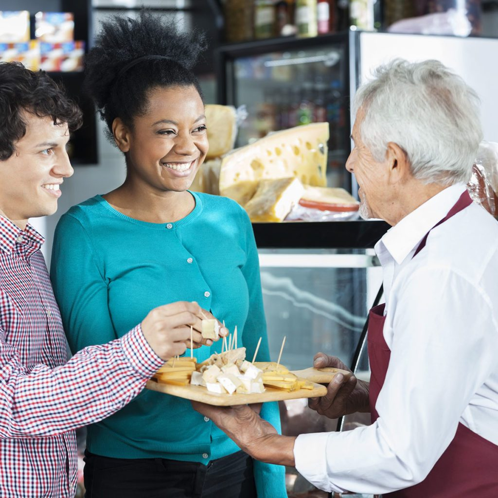 Salesman Offering Cheese Samples To Customers In Shop; Shutterstock ID 414153787; Job (TFH, TOH, RD, BNB, CWM, CM): TOH