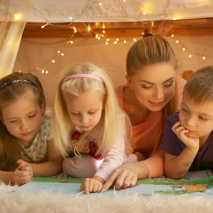 Young woman and cute children reading book in hovel at home; Shutterstock ID 598451210; Job (TFH, TOH, RD, BNB, CWM, CM): TOH