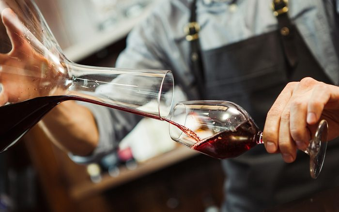 Sommelier pouring wine into glass from mixing bowl.